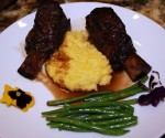 Plated short ribs over creamy polenta