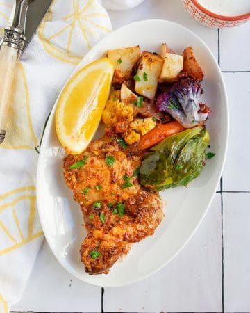 chicken and vegetables on white plate with lemon napkin