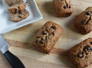 Banana Chocolate Chip Loaf on cutting board w slices on plate