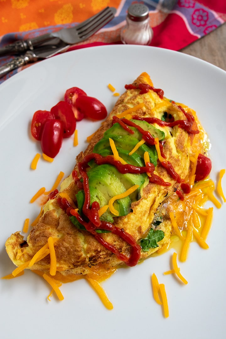 fluffy pancetta omelet with sriracha sauce and avocado on top