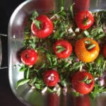 Tomatoes and herbs in a roasting pan for roasted tomato sauce