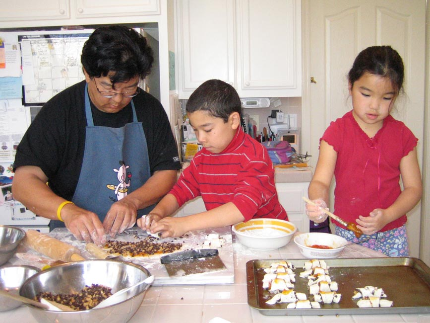 dad and two kids making rugelach on a kitchen counter