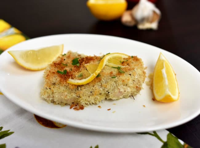 Breaded Lemon Garlic Chicken with Olive Oil on white plate with dark background and lemon napkin