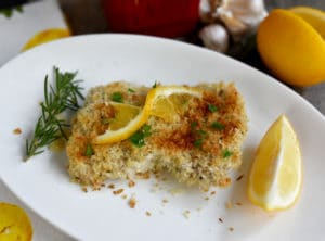 Breaded Lemon Garlic Chicken with Olive OIl on white plate with lemon and rosemary