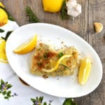 Breaded Lemon Garlic Chicken on white plate with lemon on vertical wood background