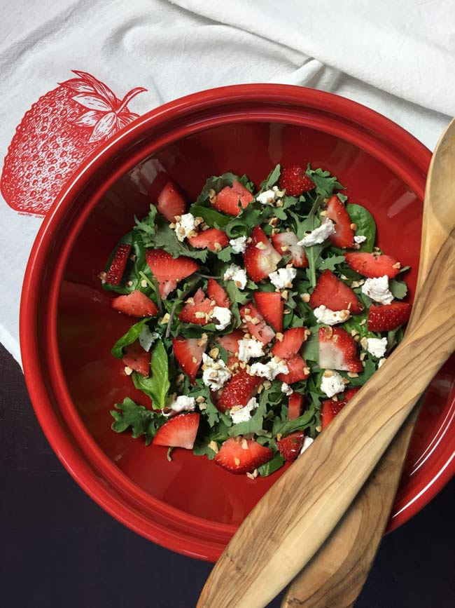 strawberry spinach salad in red bowl with wooden serving spoons