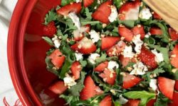 strawberry spinach salad in red bowl with serving utensils on top