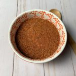 spice rub in orange bowl with wooden spoon on wood background