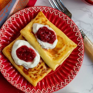2 blintzes on red plate topped with sour cream and jam
