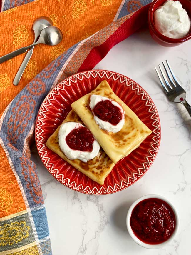 two blintzes on red plate with strawberry jam and sour cream