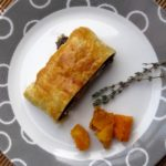 slice of vegetarian holiday entree on plate with thyme and squash
