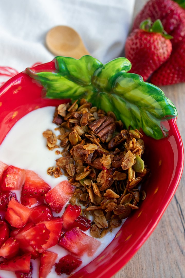 close up of olive oil granola parfait in strawberry bowl