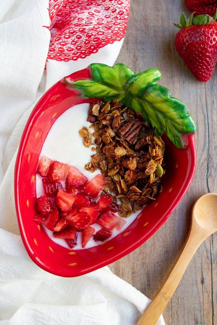 olive oil granola, yogurt and strawberries in strawberry bowl