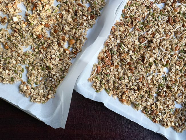 uncooked granola on two sheet trays
