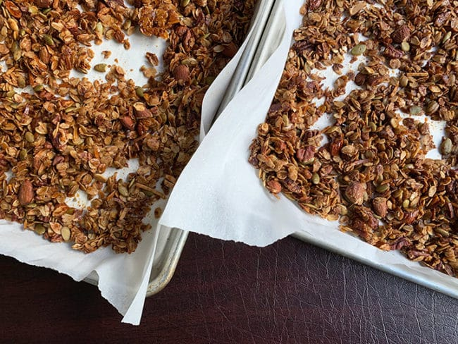 cooked olive oil granola on two sheets trays