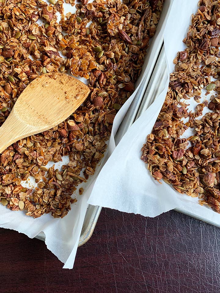 granola cooked on tray with wooden spoon