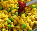 corn and edamame with red spoon