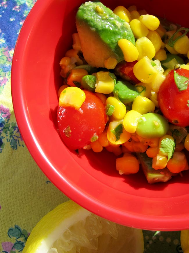 make-ahead corn salad in red bowl with sunlight