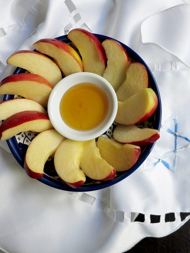 sliced apples and honey in blue bowl on white cloth