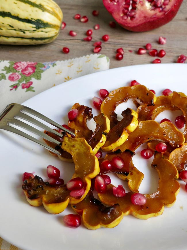 roasted delicata squash with pomegranate on white plate