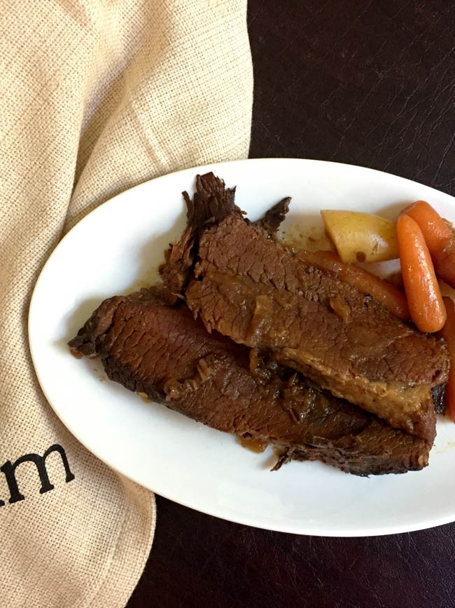slices of brisket on white plate with potato and carrots and yum napkin