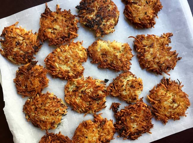 Potato Latke Recipe - potato latkes on parchment on cookie sheet