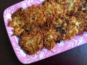 Potato Latke Recipe -- potato latkes on purple plate at an angle
