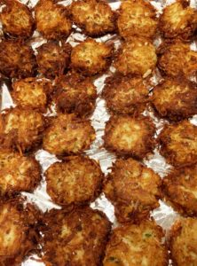 potato latke recipe - cooked latkes on foil lined pan to be reheated
