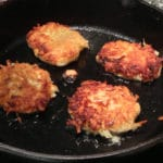Potato Latke Recipe - 4 potato latkes frying in a cast iron pan