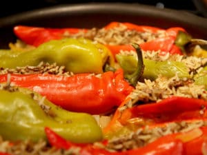 close up of red and green cooked peppers in pan