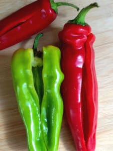 red and green peppers on bamboo cutting board