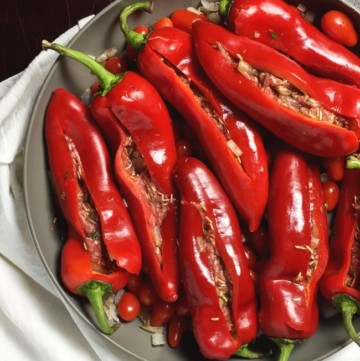 red Romano peppers stuffed and ready to cook in pan with white towel