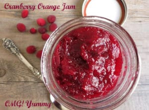 Cranberry orange jam on wood background with red words and a spoon