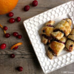 rugelach on white plate with cranberries and orange rind