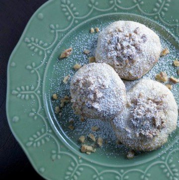 3 cookies on green plate with powdered sugar