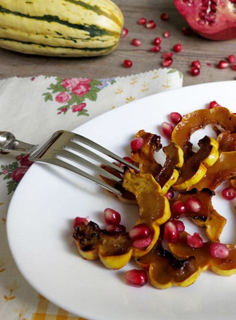 Roasted Delicata Squash with Pomegranate Molasses and Date Syrup on a white plate with whole squash and half pomegranate in the background