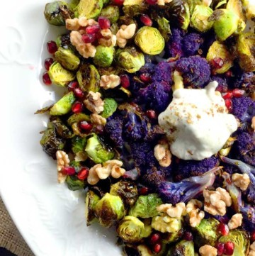 roasted brussels sprouts with yogurt topping and purple cauliflower on a white plate