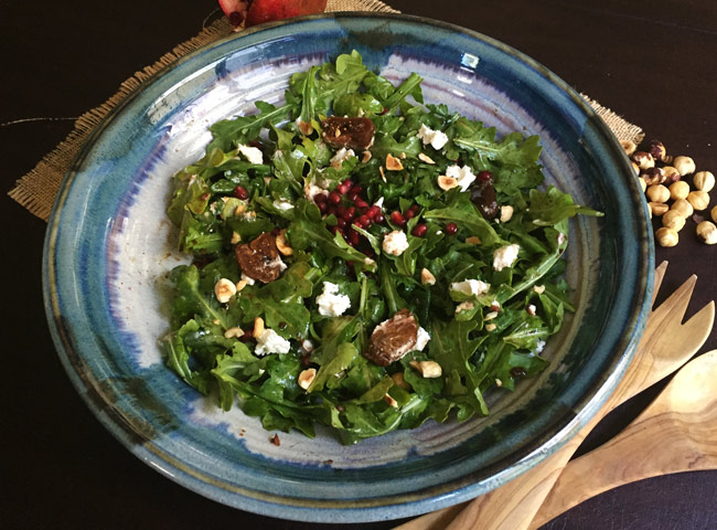 fig salad in blue bowl with serving utensils