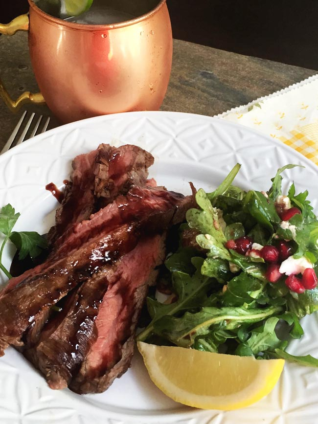 Flank steak on white plate with salad and copper mug