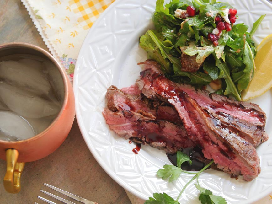 flank steak with pomegranate molasses on white plate with arugula salad