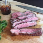 rare flank steak sliced on cutting board with pomegranate molasses