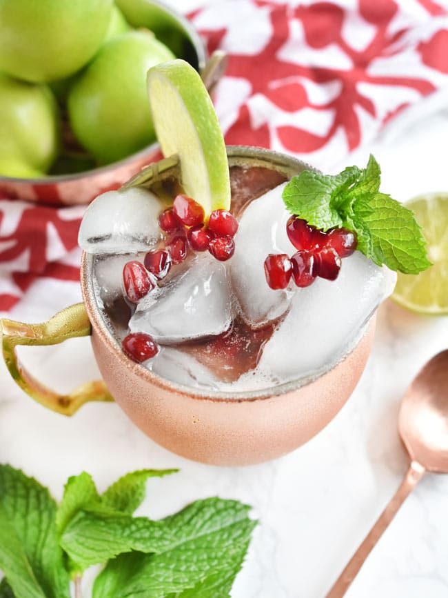 close up of pomegranate mule cocktail in a copper mug with lime and mint