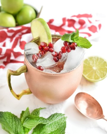 pomegranate molasses cocktail in a copper mug w limes and mint
