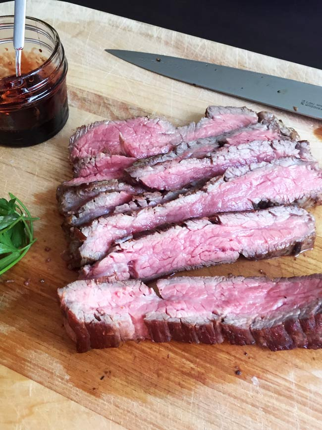 sliced flank steak on cutting board with jar of pome molasses