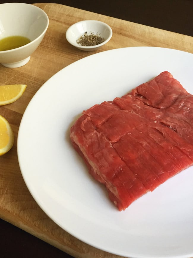 uncooked flank steak on wooden cutting board