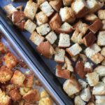 challah and cornbread cubes on sheet trays at an angle