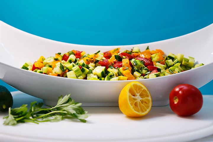 chopped salad in a white bowl with a blue background