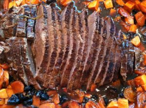 brisket in large pan with gravy and vegetables surrounding it