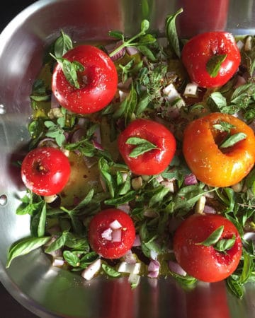 tomatoes pre-roasting in pan with herbs face down view