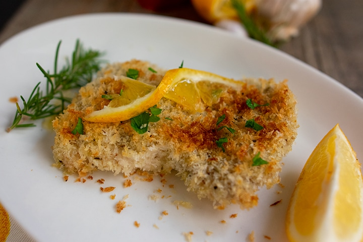 close up of lemon garlic chicken on white plate with lemon twist on top